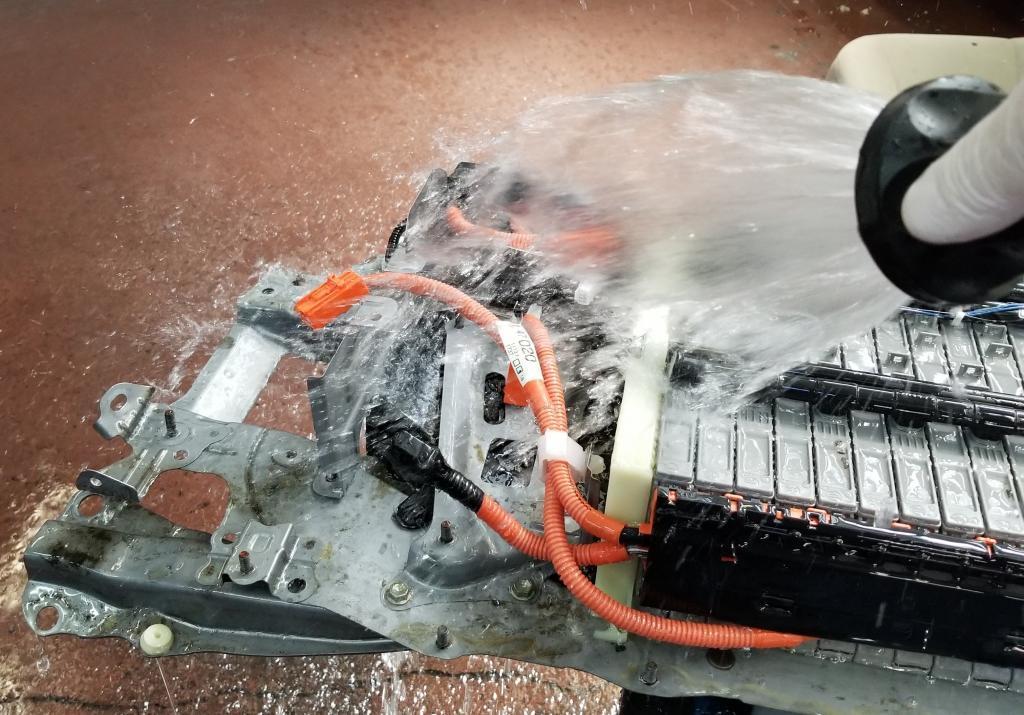 a garden hose spraying a hybrid battery