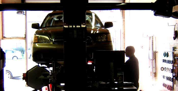 backlit image of car and mechanic performing wheel alignment
