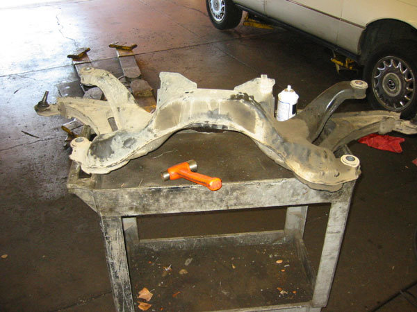subframe removed from car sitting on a cart