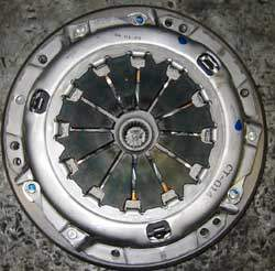 clutch pressure plate on top of a clutch disc on top of a flywheel