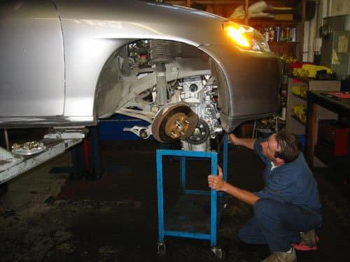 Mechanic removing Honda Insight engine