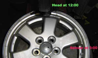Wheel on tire machine with marking showing that the TPMS sensor should be 3:00 when the head is at 12:00