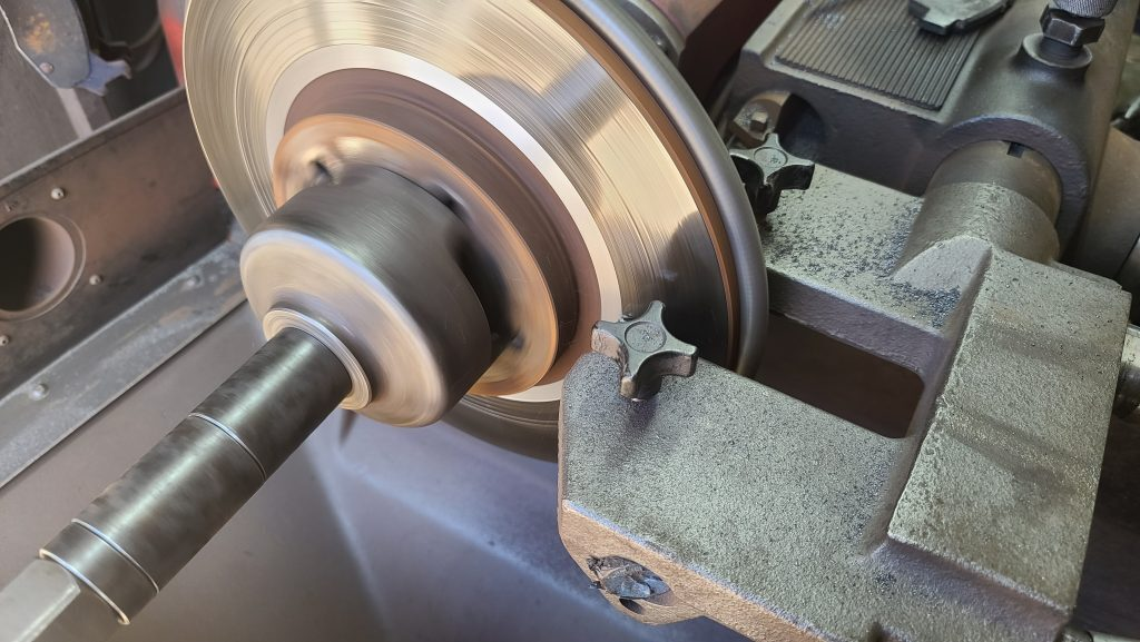 Brake rotor spinning in brake lathe with chips of metal flying off