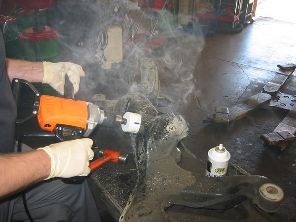 a mechanic cutting through metal with a hole saw with clouds of oil smoke