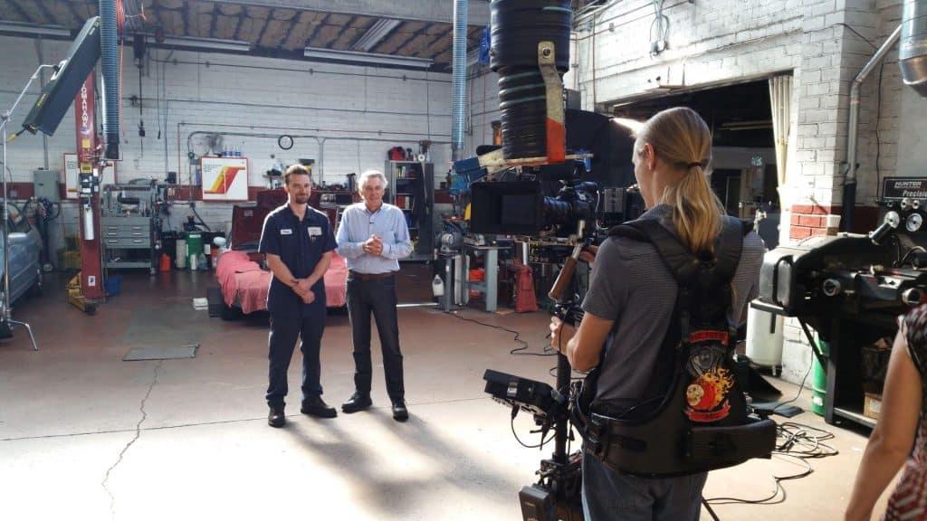 Camera crew filming Chris while making an auto repair video