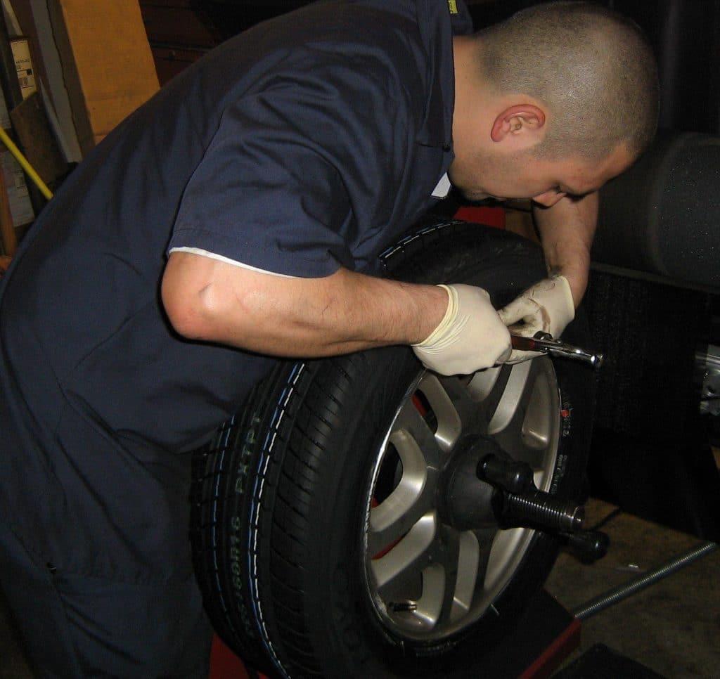 mechanic installing weights on a wheel to correct imbalance