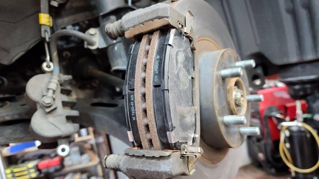 Subaru brake pads in caliper bracket with caliper removed