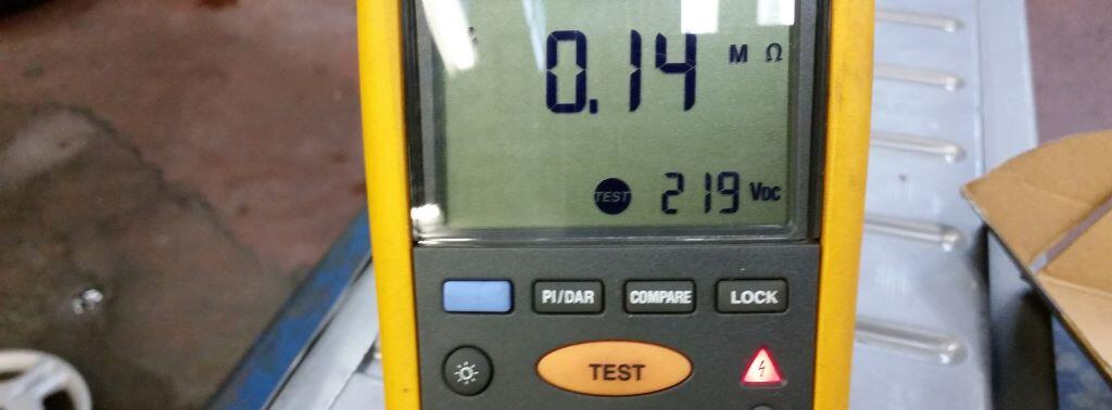 insulation test meter displaying 0.14 megohms sitting on a 2002 prius battery