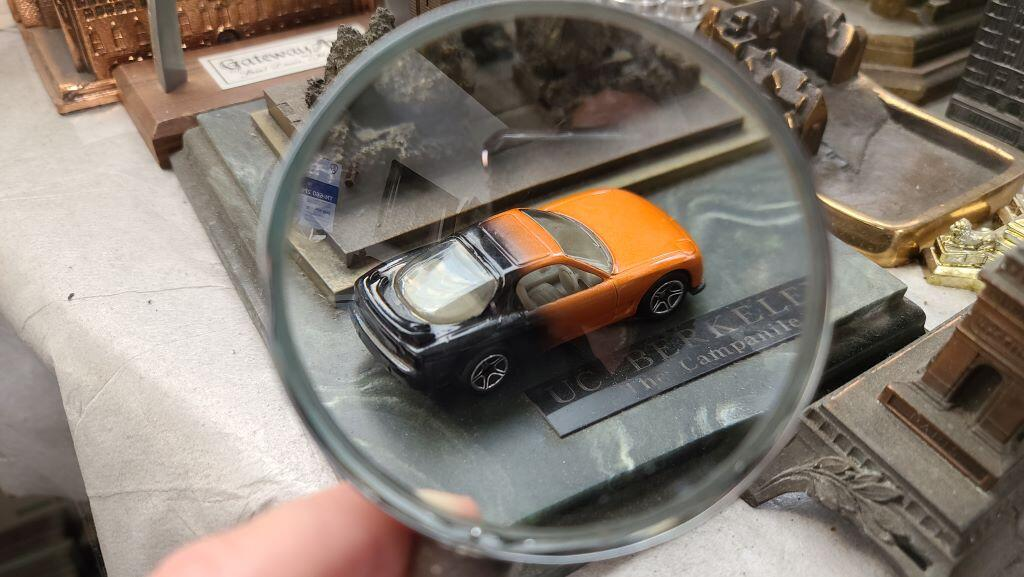 Hotwheels car being inspected with an magnifying glass