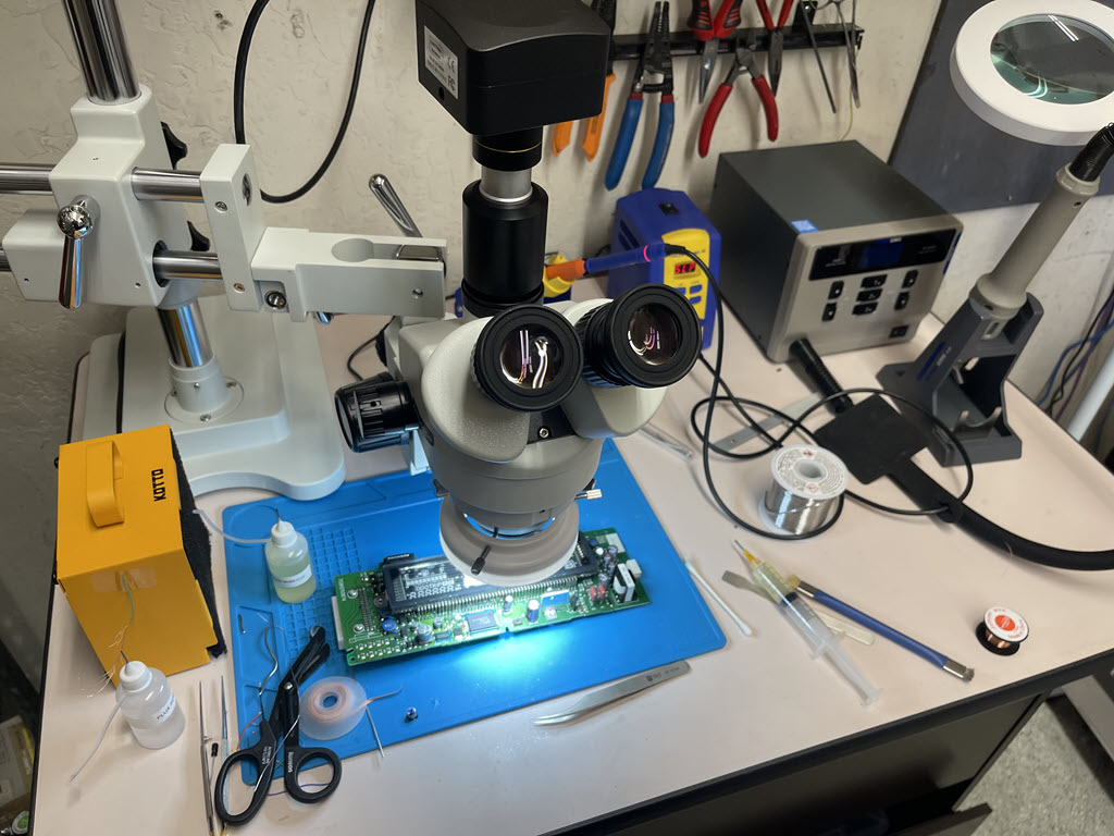 An electronics repair station with a microscope, soldering station, hot air station, fume extractor, and Prius combination meter circuit board being repaired