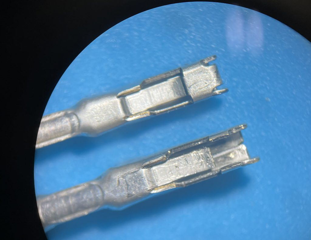One good terminal and one damaged terminal under a microscope