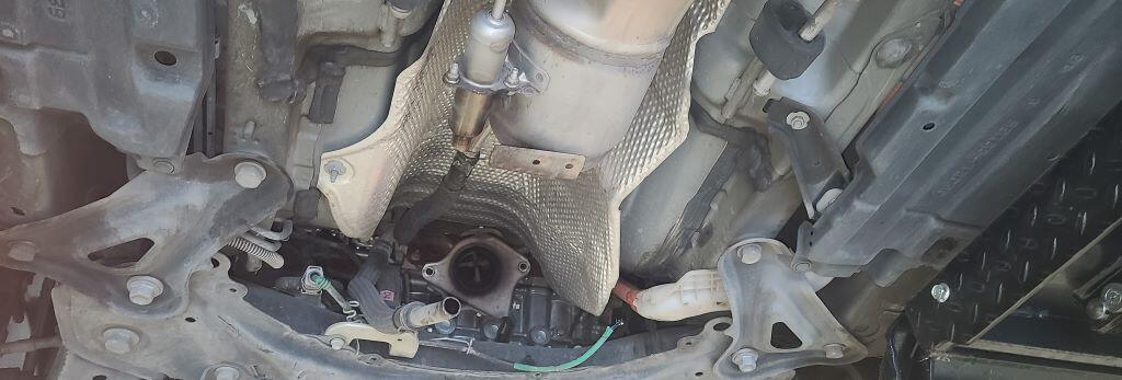 The underside of a 2012 Prius with the catalytic converter sawed out.