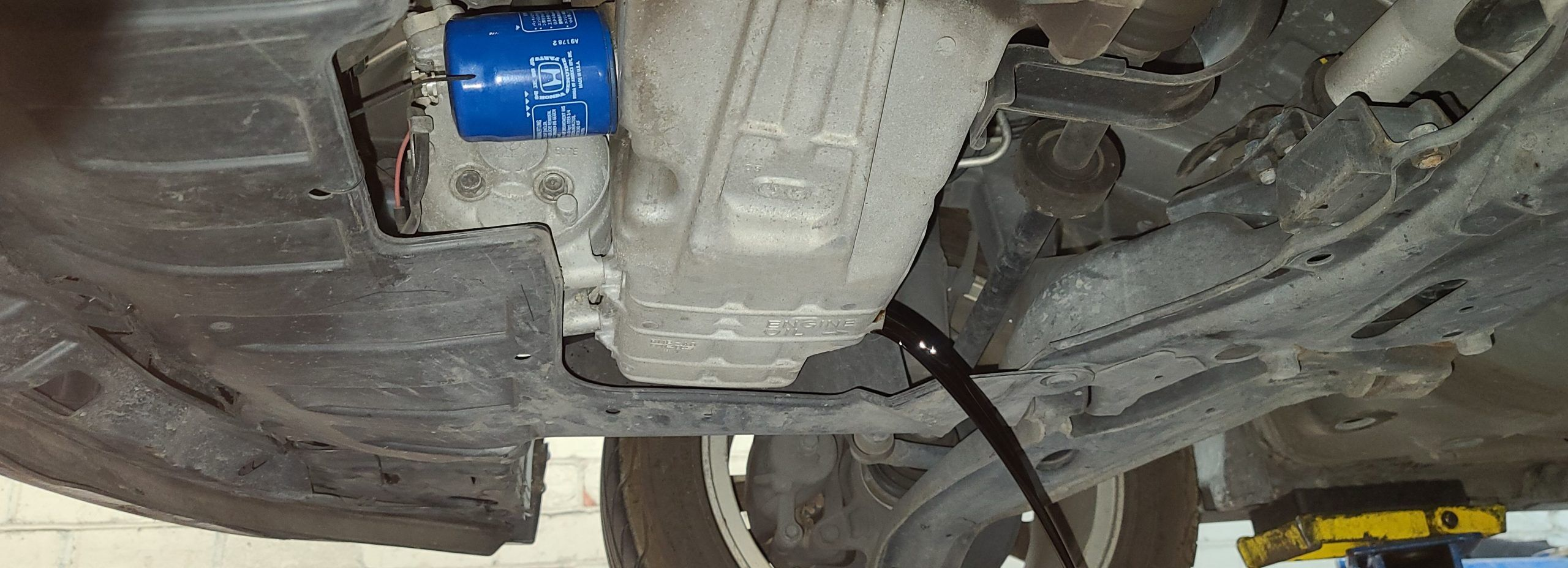 the underside of a car with motor oil draining from the oil pan.