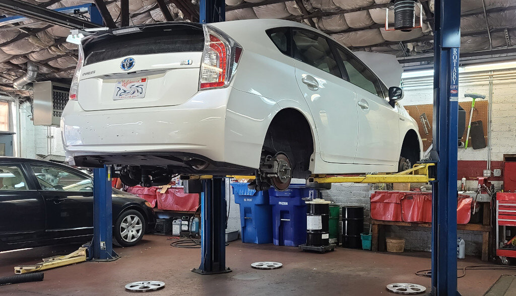 Toyota Prius sitting on a rack in a repair shop
