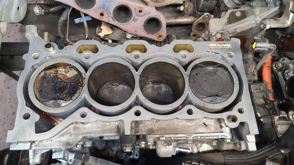Prius engine block with cylinder head removed. One piston crown is cleaner than the others due to a leaking head gasket.